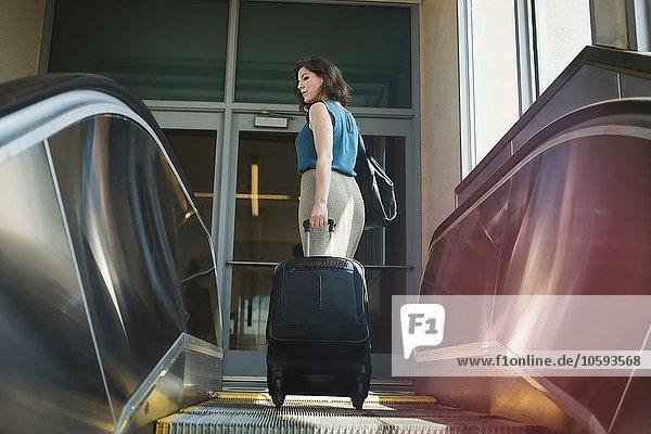 Mittlere erwachsene Frau mit Rolltreppe  Rollkoffer haltend  Rückansicht