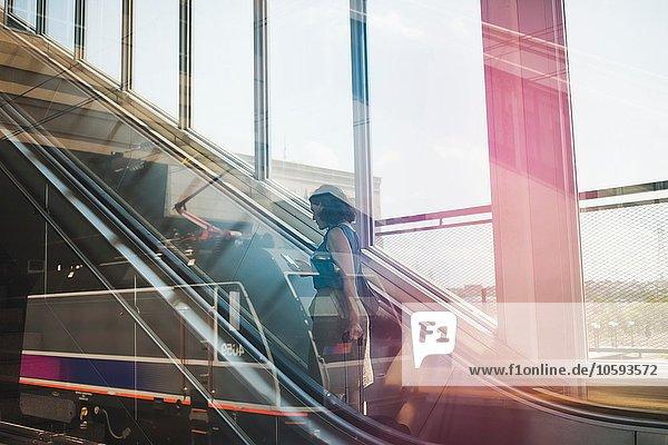 Mittlere erwachsene Frau mit Rolltreppe  fahrbarem Koffer und Smartphone