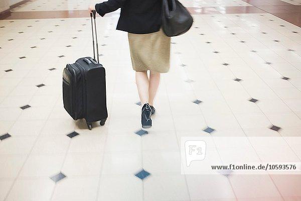 Mittlere erwachsene Frau beim Gehen mit Rollkoffer  Rückansicht  niedrige Sektion
