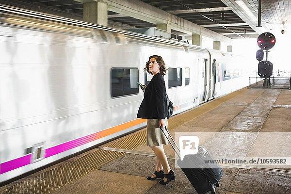 Mittlere erwachsene Frau  die auf den Zug wartet  mit Rollkoffer und Smartphone