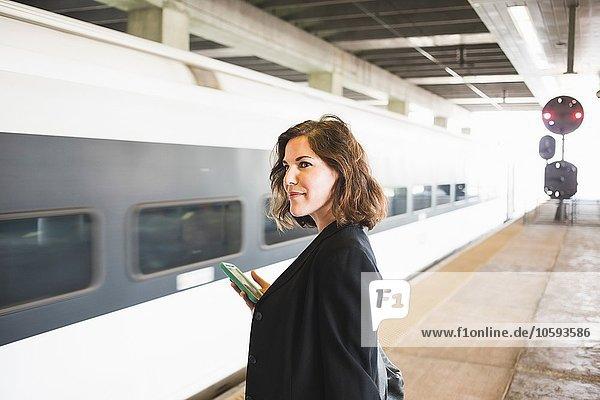 Mittlere erwachsene Frau  die auf den Zug wartet und ein Smartphone hält