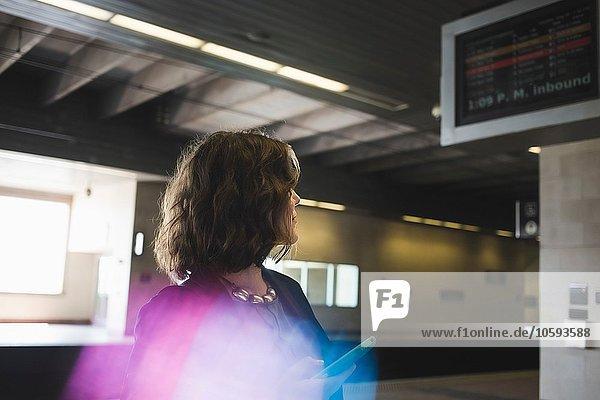 Mittlere erwachsene Frau am Bahnhof  Smartphone haltend
