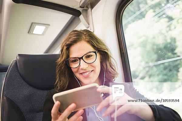 Mittlere erwachsene Frau im Zug  mit Smartphone  Kopfhörer tragend