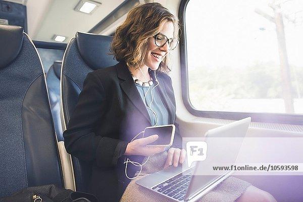 Mittlere erwachsene Frau im Zug  mit Smartphone und Laptop