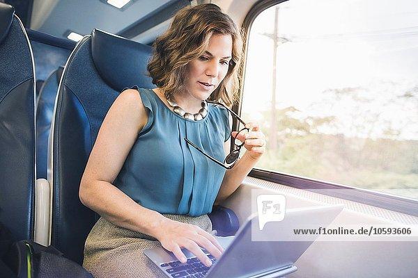 Mittlere erwachsene Frau im Zug  mit Laptop