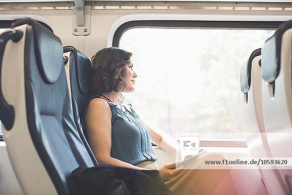 Mittlere erwachsene Frau im Zug  mit digitalem Tablett  Blick aus dem Fenster