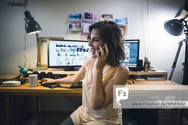 Mid adult woman at desk  using smartphone