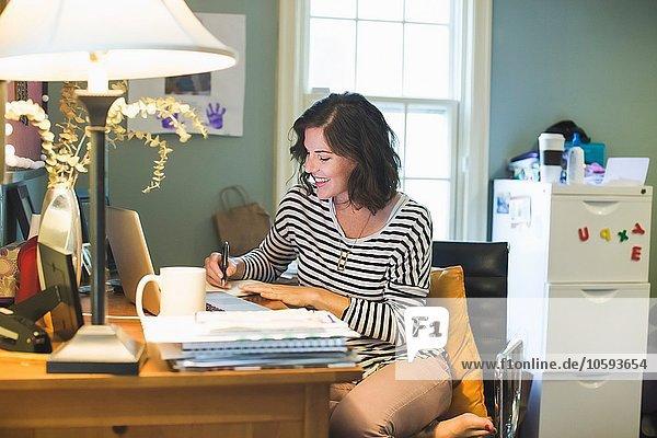 Mittlere erwachsene Frau am Schreibtisch  Laptop und Kaffeetasse vor ihr  Schreiben im Buch