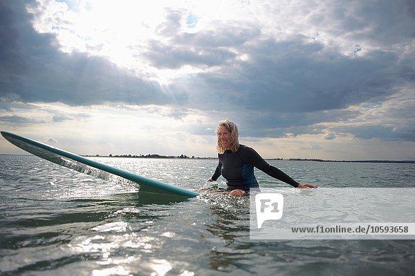 Porträt einer älteren Frau  die auf dem Surfbrett im Meer sitzt  lächelnd