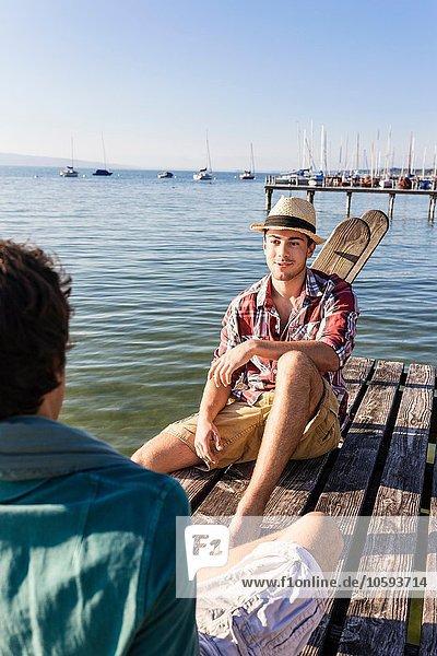 Freunde sitzen von Angesicht zu Angesicht auf einem Holzsteg am See  Schondorf  Ammersee  Bayern  Deutschland