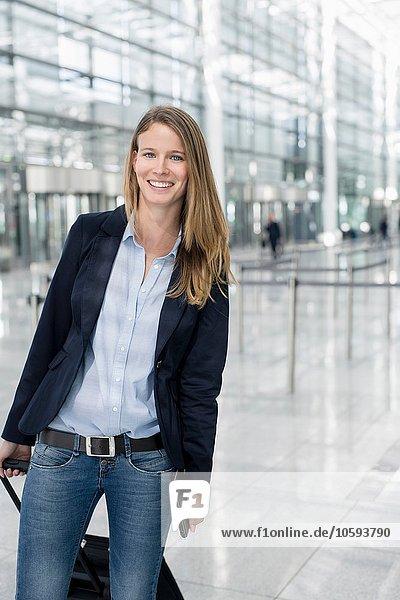 Portrait einer jungen Geschäftsfrau am Flughafen mit Rollkoffer