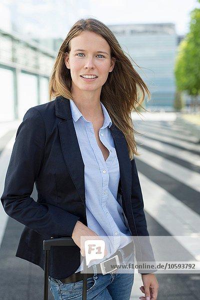 Porträt einer jungen Geschäftsfrau mit Rollkoffer am Flughafen