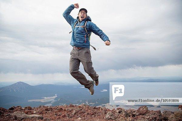 Junger Mann springt vor Freude auf dem Gipfel des South Sister Vulkans  Bend  Oregon  USA