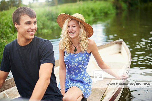 Junges Paar im Ruderboot auf dem Landfluss