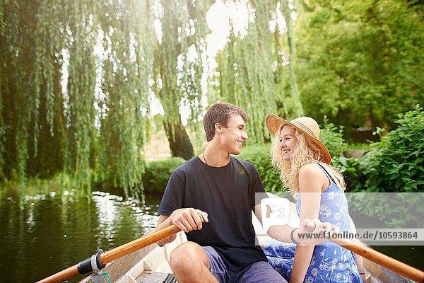 Romantisches junges Paar im Ruderboot auf dem Landfluss