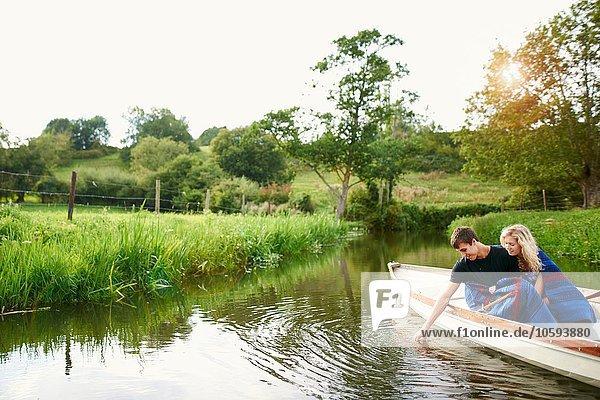 Junger Mann mit Freundin beim Berühren von Wasser aus dem Fluss-Ruderboot