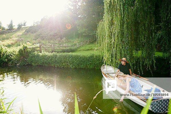 Junge Frau mit Freund beim Berühren von Wasser aus dem Fluss-Ruderboot