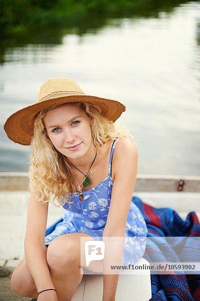 Porträt einer jungen Frau mit langen blonden Haaren im Flussboot