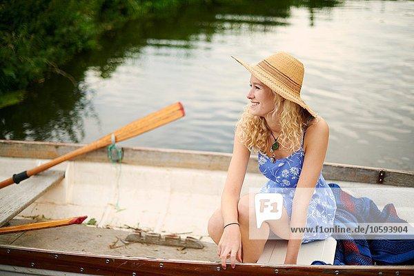 Porträt einer jungen Frau mit langen blonden Haaren im Ruderboot auf dem Fluss