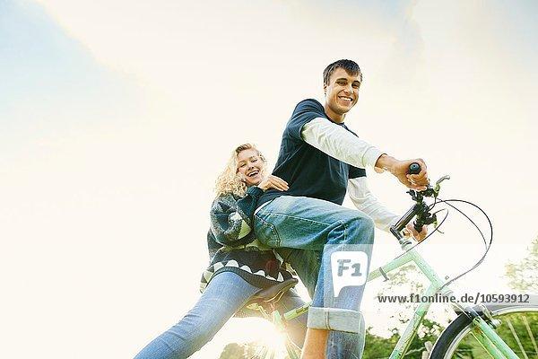 Niederwinkel-Porträt eines jungen Paares auf dem Fahrrad
