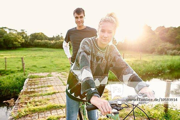 Porträt eines jungen Paares auf dem Fahrrad an der Flussbrücke