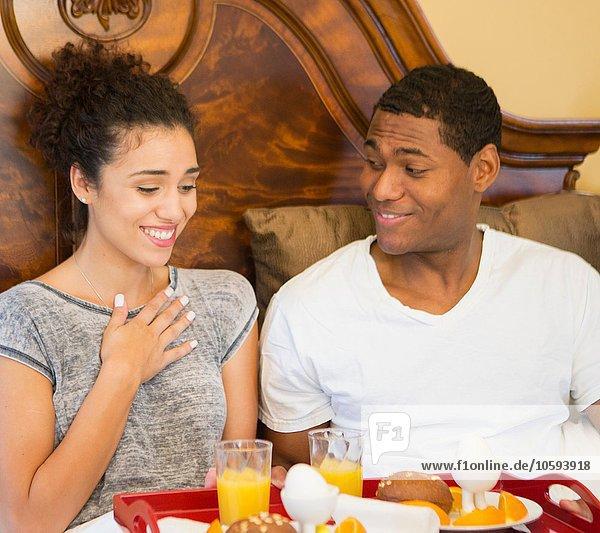 Mittlerer Erwachsener Mann überrascht junge Frau mit Frühstück im Bett