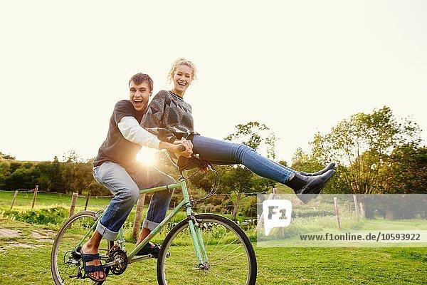 Junge Frau sitzt auf dem Fahrradlenker eines Freundes