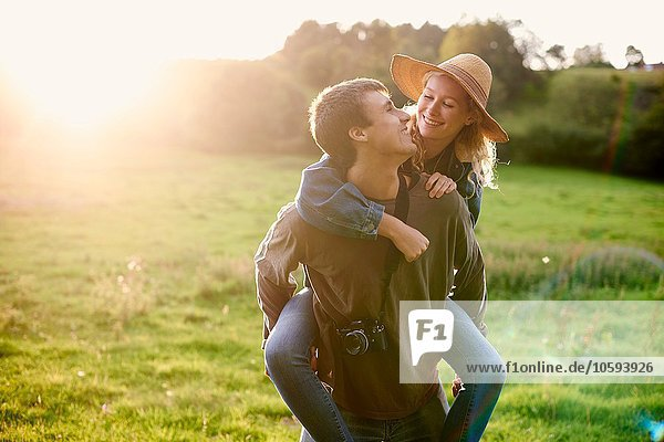 Junger Mann gibt Freundin ein Huckepack im ländlichen Raum