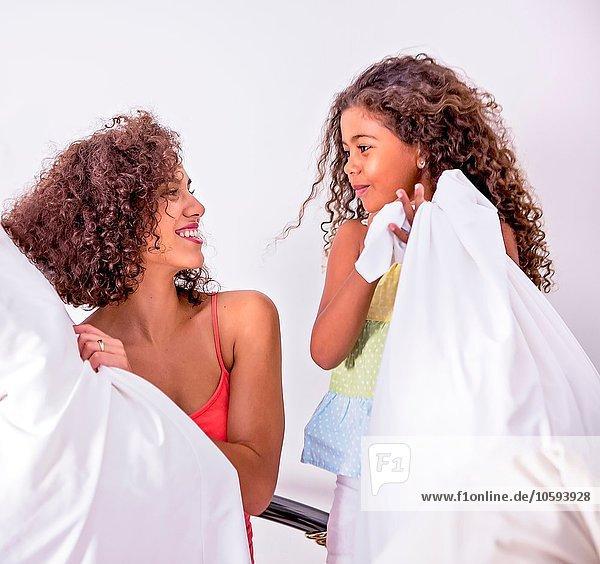 Mutter und Tochter halten die Kissen von Angesicht zu Angesicht lächelnd.
