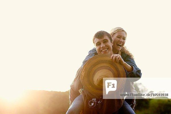 Porträt eines jungen Mannes  der seiner Freundin ein Huckepack gibt.