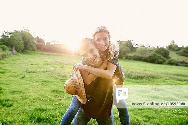 Porträt eines jungen Mannes  der seiner Freundin ein Huckepack im ländlichen Raum schenkt.