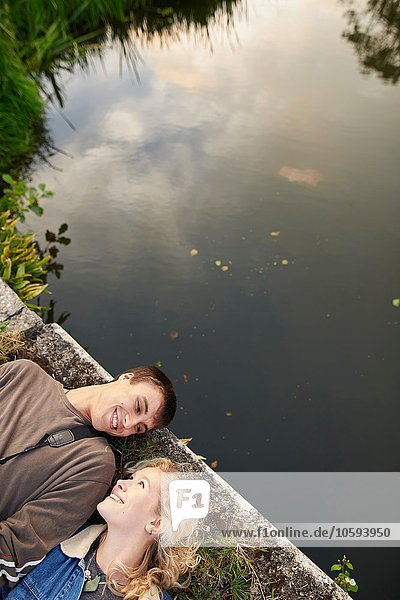 Draufsicht auf ein junges Paar  das auf einer Flussbrücke liegt.