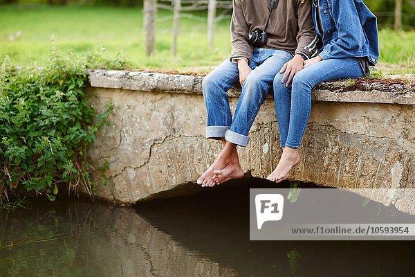 Nackenansicht eines jungen Paares  das auf einer Flussbrücke sitzt.