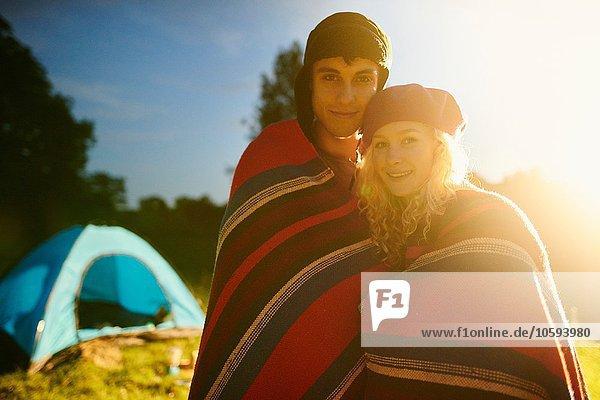 Porträt eines jungen  romantischen Campingpaares  das bei Sonnenuntergang in eine Decke gehüllt ist.