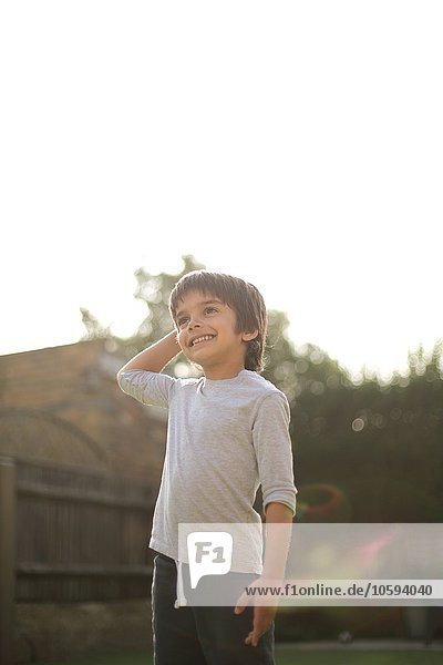 Niedriger Blickwinkel des Jungen in der Gartenhand auf den Kopf,  der lächelnd weg schaut