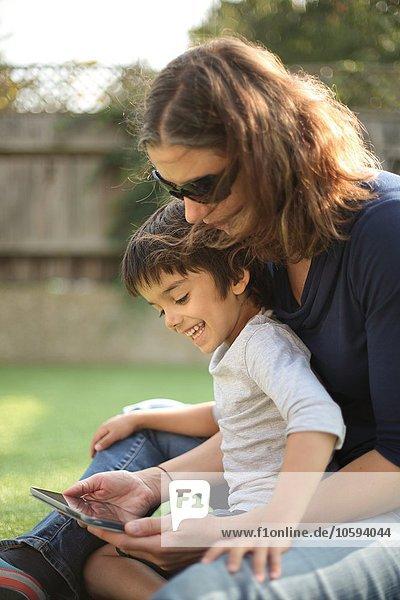 Seitenansicht des Jungen,  der auf dem Schoß der Mutter sitzt,  mit einem digitalen Tablett,  das lächelnd nach unten schaut.