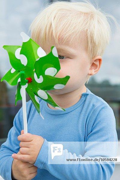 Männliches Kleinkind bläst Pinwheel vor seinem Gesicht auf der Terrasse