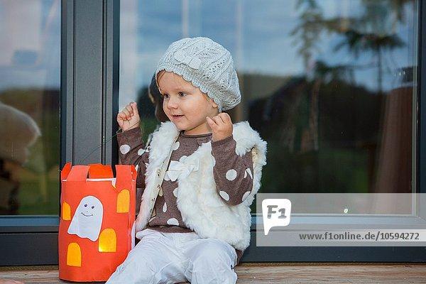 Kleinkind auf Fensterbank sitzend mit hausgemachter Halloween Laterne
