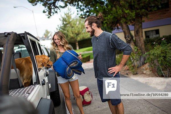 Junges Paar und Hund bereiten sich auf die Beladung des Jeeps für die Fahrt vor.