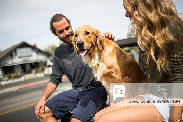 Junges Paar mit Hund im Jeep sitzend
