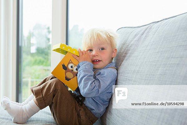 Portrait eines männlichen Kleinkindes beim Spielen mit Bausteinen auf dem Sofa