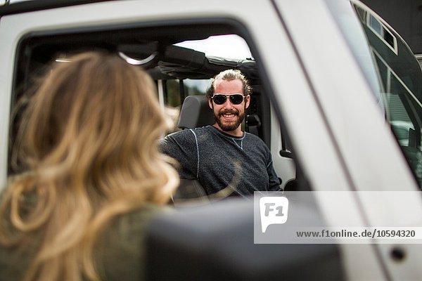 Über die Schulteransicht einer jungen Frau  die mit ihrem Freund im Jeep chattet.