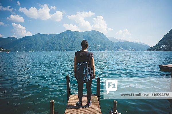 Rückansicht der mittleren erwachsenen Frau mit Blick vom Pier  Luganer See  Schweiz