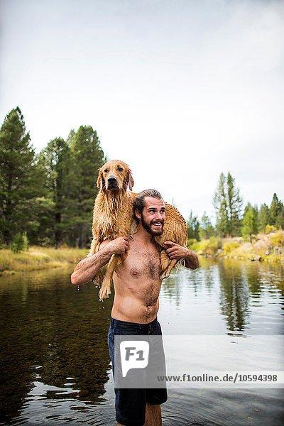 Junger Mann mit nassem Hund über den Schultern im Fluss  Lake Tahoe  Nevada  USA