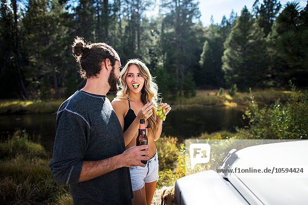 Young couple eating grapes on riverside  Lake Tahoe  Nevada  USA