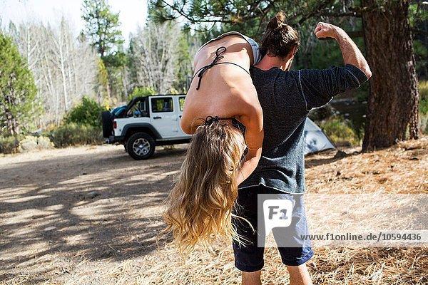 Rückansicht des jungen Mannes  der seine Freundin über die Schulter trägt  auf dem Waldcampingplatz Lake Tahoe  Nevada  USA.