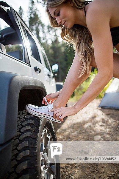 Junge Frau mit Schnürsenkeln am Jeep  Lake Tahoe  Nevada  USA