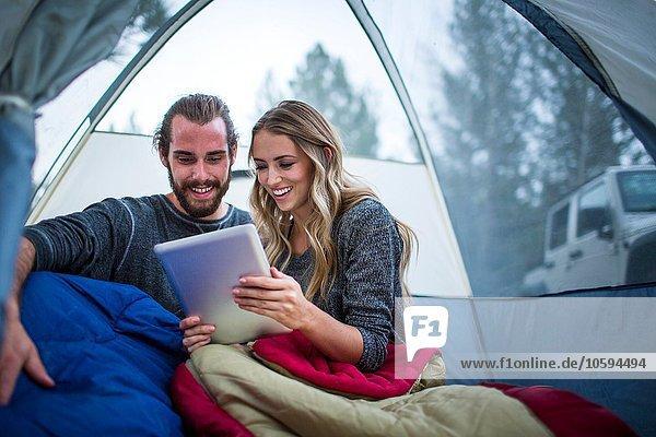 Junges Paar liest digitales Tablett im Zelt  Lake Tahoe  Nevada  USA