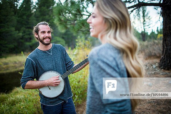 Junges Paar spielt Banjo am Flussufer  Lake Tahoe  Nevada  USA
