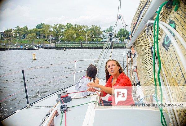 Junge Frau  die das Segel auf dem Segelboot verstellt  schaut nach oben.